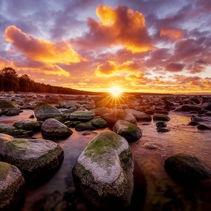Colorful rocky beach at sunset with warm colors and beautiful sky