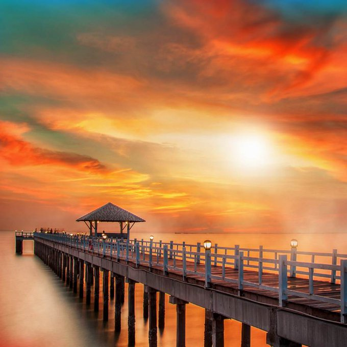 Colorful sky at sunset on the sea beach with wooden bridge