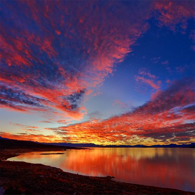 Bright red sunset over a calm lake with mountains in the background