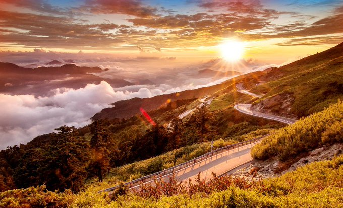 Beautiful mountain road above the clouds at sunset