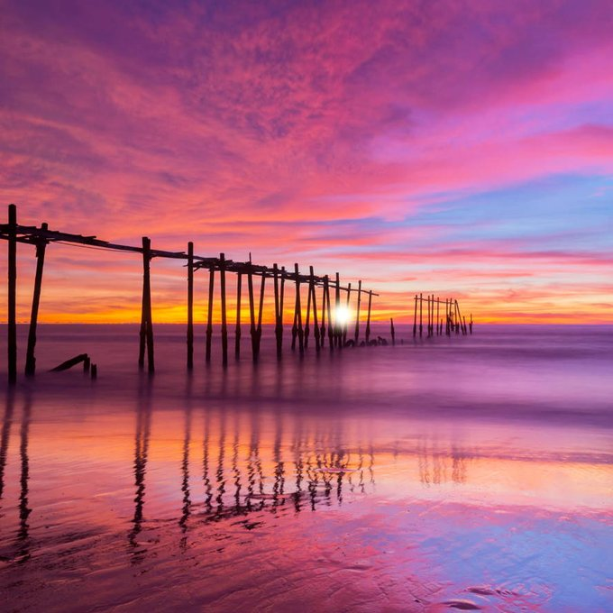 Soft sea waves on the sand beach with old wood bridge at sunset
