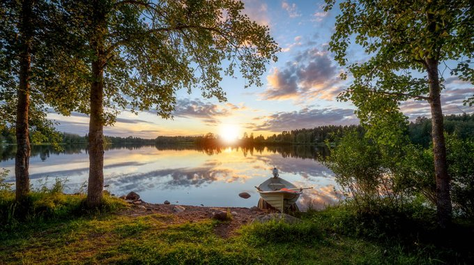 Tranquil clean lake surrounded by fresh green forest in Lapland Finland