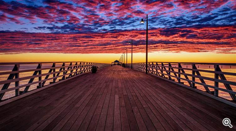 Gorgeous sky and clouds over the pier and ocean at sunset