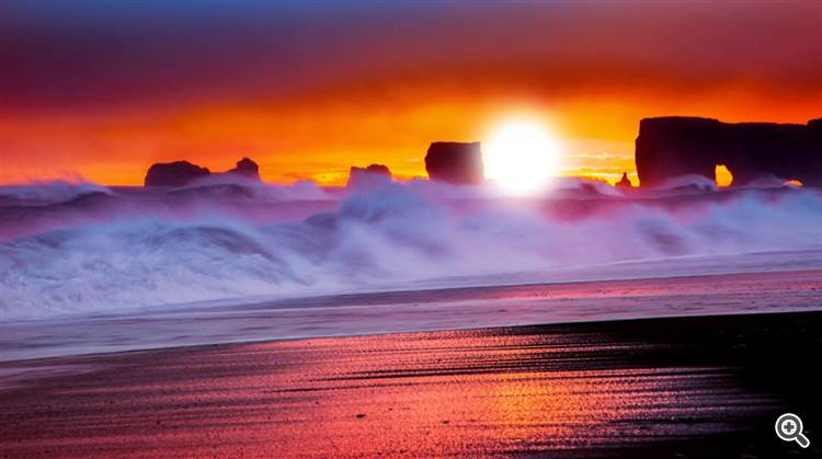 Ocean waves crashing into a rocky shore under an orange red sky at sunset