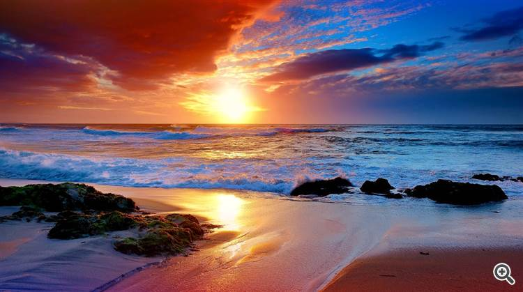 Tranquil beach and ocean waves under gorgeous orange sky at sunset