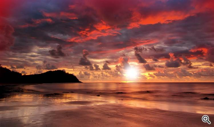 Gorgeous sunset with colorful red sky over the tranquil beach