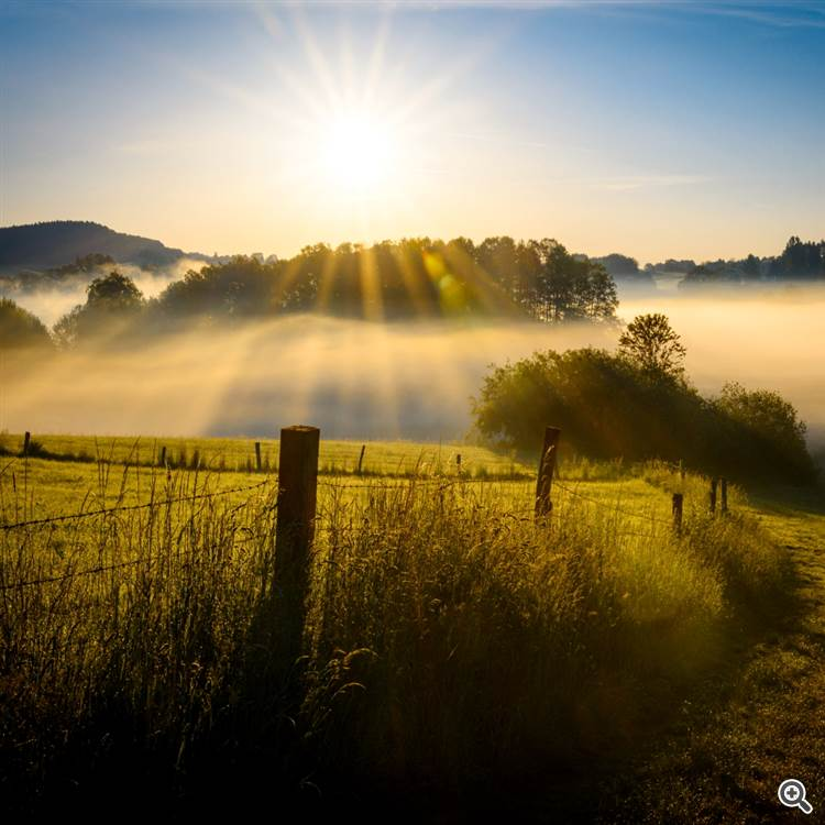 Magical sunrise over sea and countryside