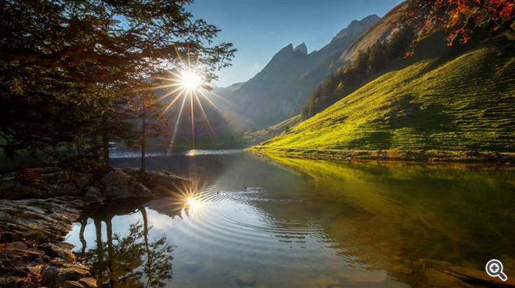 Soft sunlight over mountains and calm alpine lake