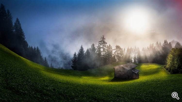 Mountain hut in the foggy misty forest